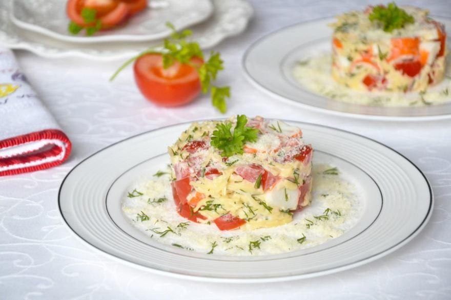 Сервировка вкусного крабового салата с помидорами и сыром